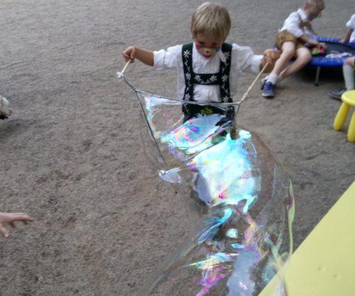 Zum Kindergeburtstag Seifenblasen machen.